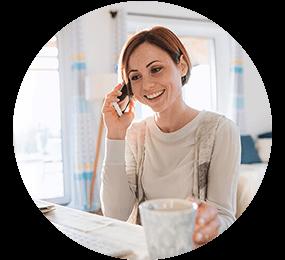 Frau telefoniert mit einem Smartphone am Laptop und hält einen Becher in der Hand