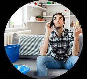 Mann blickt verzweifelt und telefoniert auf einer grauen Couch mit Schüsseln vom Wasserschaden